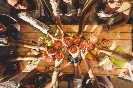 Above view group of friends people enjoy food and drinks toasting and clinking with red wine glasses all together having. fun - celebration and friendship concept - coloured background Stok Fotoğraf
