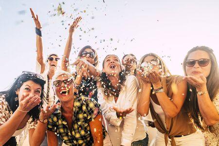 Gente divirtiéndose en el concepto de amigos de celebración de fiestas - grupo de mujeres jóvenes y adultas todas juntas riendo soplando confeti de colores - amistad y amor por el estilo de vida con generaciones activas mixtas