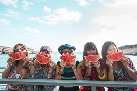 Summer lifestyle concept with group of trendy people cheerful happy women enjoying the outdoor leisure acitivty with red fresh watermelon - sea in background