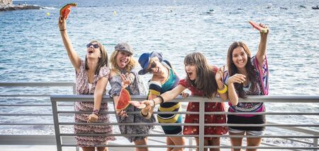 Group of crazy females friends have fun outdoor with watermelon and friendship - people on vacation enjoy and laugh a lot with joyful together - blue ocean in background Stok Fotoğraf