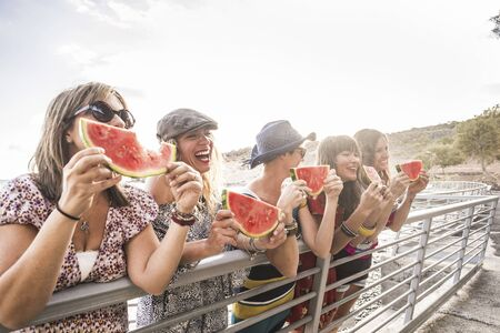 Friendship and have fun outdoor concept with people group of cheerful happy girls eating watermelon during summer vacation and leisure activity - laughing a lot beautiful caucasian females Stok Fotoğraf