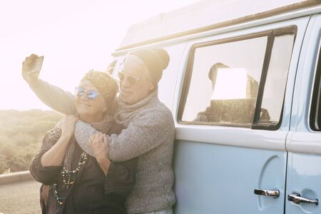 Travel and alternative people vacation concept for senior retired lifestyle couple taking selfie picture for social media - vintage van in background - sunset sunlight and forever concept Stok Fotoğraf