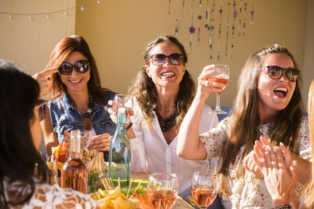Group of caucasian people women friends celebrate together with table full of food and toasting with red wine - happiness and friendship for adult and young females at restaurant or home Stok Fotoğraf
