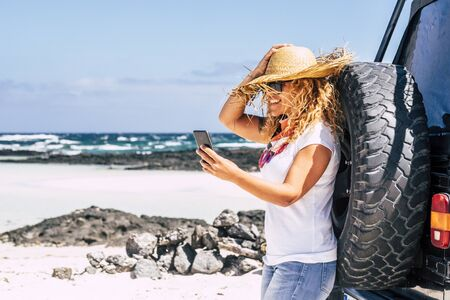 Alternative happy independent traveler people - cheerful happy woman with off road car enjoy the beach and the summer holiday vacation taking a picture with phone - beach ocean and nature Stok Fotoğraf