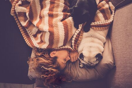 Love concept with dog animals and people- beautiful sweet woman sleep at home on the sofa with her two lovely best friend pugs near her to pretect and enjoy the friendship. pet therapy concept
