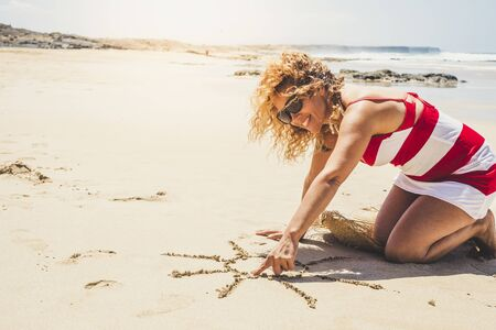 Happy cheerful woman on summer holiday vacation enjoying the beach and the outdoor designing a sun on the sand - beautiful curly caucasian people lady in outdoor leisure activity