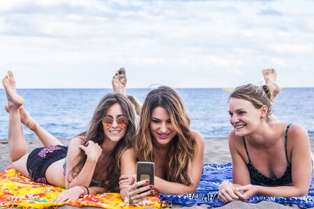 Summer concept with group of three beautiful girls in friendship stay lay down relaxed at the beach speaking and using a smartphone to share her summer lifestyle with friends at home.