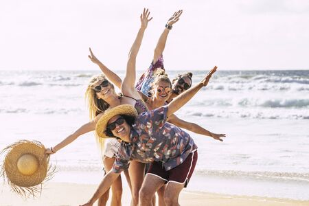 Happy cheerful group of young people friends having fun together in friendship at the beach with sea in background - tourism travel trousit concept with youthful and joyful lifestyle