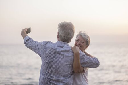 Romantic people couple of senior man and woman hugging and taking a selfie picture with mobile phone in front of the sea - vacation for elderly free lifestyle concept - woman looking behind and smile