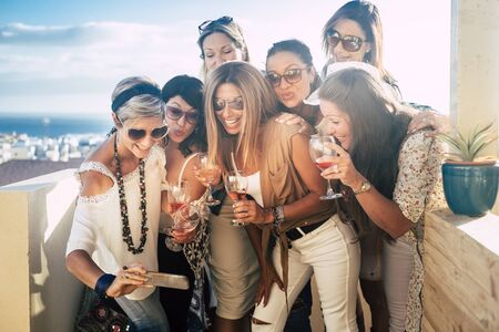 Happy and cheerful people young beautiful women look a picture on a smartphone having fun - outdoor celebration concept for friends together - blue sea in background and smiles Stok Fotoğraf