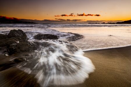 Long exposure sea beach sunset landscape with wave and coloured sunset with orange sky - beauty of the nature and timeless vacation in tropical ocean scenic place concept