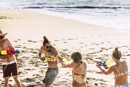 Youthful and people having fun outdoor at the beach for tropical summer holiday vacation at the sea - playing with water guns all together - couples and joyful concept