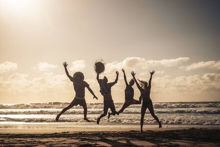 Group of people jump happy together at the beach during sunset with sky in background and silhouette bodies - summer vacation holiday for friends people have fun in outdoor leisure activity Stok Fotoğraf