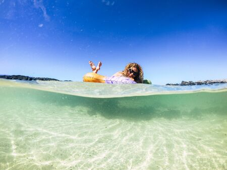 Cheerful tourist people young woman enjoying her trendy new inflatable mattress in the transparent sea water on a sandy beach during summer holiday vacation - travel and lifestyle concept Stok Fotoğraf