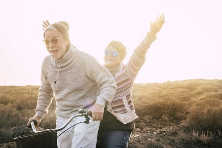 Happiness for active senior retired people lifestyle concept - joy old aged caucasian couple riding together a bika laughing and smiling a lot and having fun - outdoor leisure activity - sunset sunlight Stok Fotoğraf