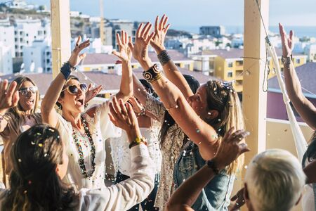 Group of happy young people caucasian women with terndy fashion clothes celebrate together with a lot of fun with coloured confetti and nice scenic view on the city from rooftop- happiness and joyful party