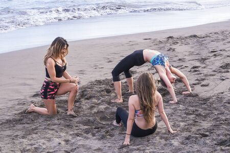 Personal trainer and class of pilates at the outdoor beach with three beautiful young girls enjoying the sport active exercises together - concept of healthy lifestyle and fun with fitness Stok Fotoğraf