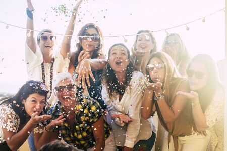 Group of people celebrate together having a lot of fun blowing coloured confetti - friendship and diversity ages generation laugh and smile on party - cheerful joyful concept for ladies Stok Fotoğraf