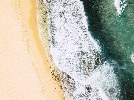 Above vertical view of blue ocean waves and yellow sandy beach - summer holiday vacation concept - travel and scenic place - energy nature outdoors with nobody there Stok Fotoğraf