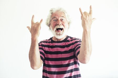 Senior people caucasian man do rockn roll signs with crazy funny expression portrait - happy mature retired lifestyle have fun with no limit age - white background studio shot