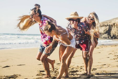 Happiness and joyful group of young hipster couples people enjoying the outdoor at the beach playing and having fun together in friendship - happy men and women on vacation friends Stok Fotoğraf