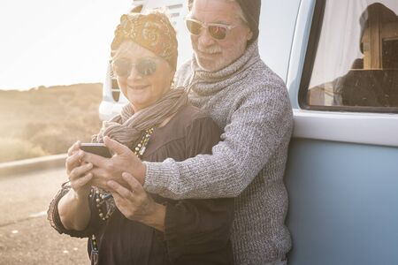 Happy cheerful retired lifestyle old youth people looking together a modern phone in outdoor travel leisure activity concept - hippy coloured happy style - vintage van in background