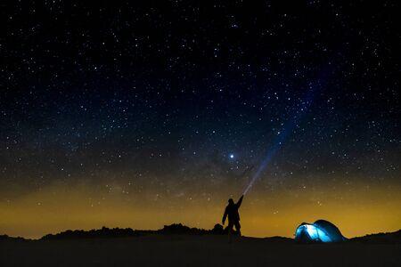 Cielo nocturno con estrellas y silueta de un hombre feliz de pie con luz azul. Fondo del espacio - concepto de personas de viaje - camping gratuito y aventuras al aire libre - descubre el estilo de vida del mundo