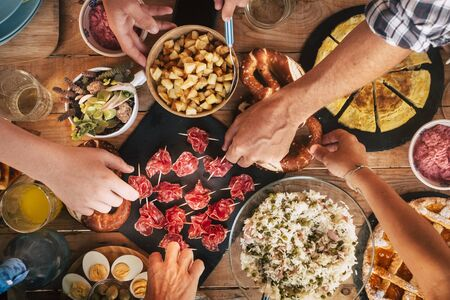 친구 개념을 즐기는 사람들 - 맛있는 음식으로 가득 찬 꼭대기 전망 테이블과 함께 식사를 하고 함께 먹기 위해 서빙하는 친구들과 함께 맛있는 점심 또는 저녁 식사 개념 - 색깔과 나무 배경