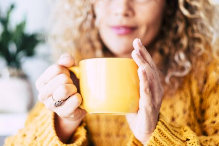 Close up on cup with tea or coffe drink inside and beautiful defocused woman in background - concept of relax and healthy lifestyle with nice people - yellow colors mood 版權商用圖片