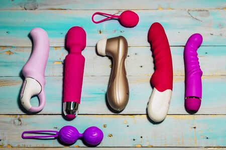 Different coloured and modern toys (dildo, love balls, butt plug, wand massager and other) are on a blue wooden trendy background. Concept of play and love yourself and have fun free
