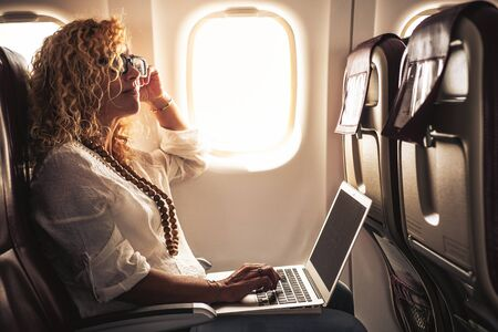 Business adult beautiful curly blonde woman travel on airplane connected to internet with modern computer laptop - people on work everywhere and digital nomad free lifestyle concept -flight on boad services 版權商用圖片