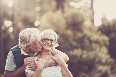 Couple of happy and cheerful people caucasian senior hug with love and smile with defocused green forest in background - outdoor leisure activity for retired matures- happiness for old Banque d'images
