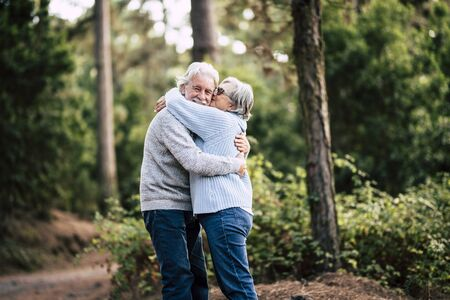 Couple of happy and cheerful people caucasian senior hug with love and smile with defocused green forest in background - outdoor leisure activity for retired matures- happiness for old