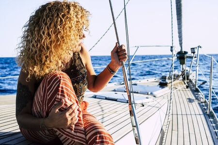 Travel and luxury lifestyle concept wtith beautiful blonde curly attractive woman sitting on the dock of a sail boat - people enjoying vacation at the sea cruising in the blue ocean