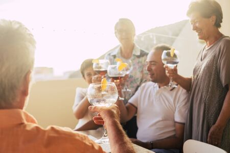 Party cocktail concept with adult caucasian group of people mixed ages and generations having fun together outdoor - focus on glass with transparent drink Stock Photo