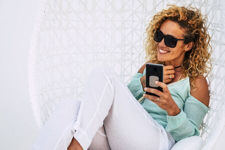 Cheerful beautiful curly young adult woman use mobile phone outdoor sit down on a white garden elegant chair -smile and enjoy the outdoor technology leisure activity 스톡 콘텐츠
