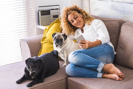 Cheerful woman at home sit down on the sofa with her two best friends dog pug near her - real lifestyle people with animals Foto de archivo