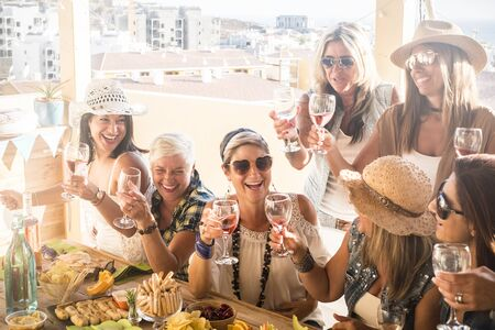 group of people or seven women together having fun and enjoying - friendship of ladys with glass of wine - wooden table full of food in the terrace at home