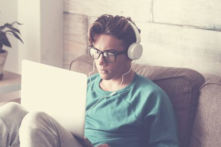 Young student at home with modern laptop computer and headphone studying with internet cnnection - handsome boy sitting on the sofa with technology indoor