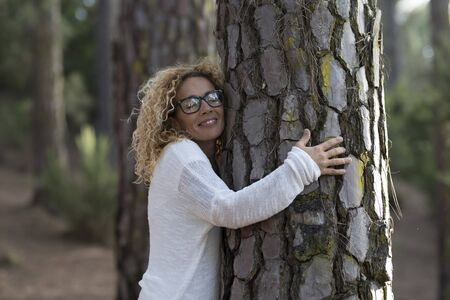 one woman hugging with close eyes a old tree on the forest - love and affection at the wood - save the forest and climate change concept - respect nature outdoor people