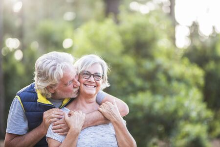 couple of two old people together hugged at the wood or forest - love concept and defocused background - married seniors enjoying the outdoors with kiss and relationship