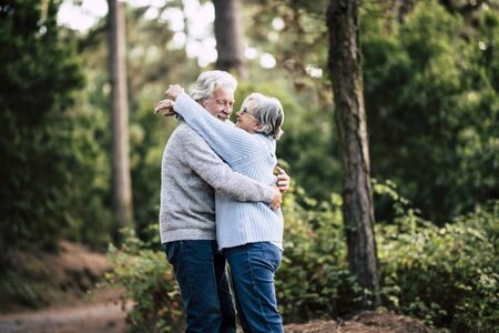 Senior active couple enjoying the outdoor nature forest with hugs and love together - forever life concept with mature man and woman - elderly and beautiful forest green in background