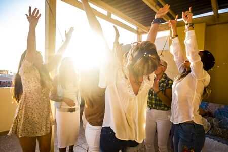 Active happy group of young free caucasian people woman celebrate and dance all together with friendship - sunset in backlight for party at home concept - Happiness for group 写真素材