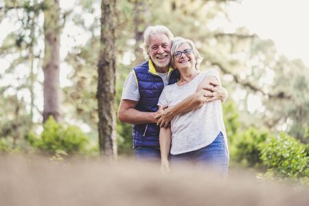 Couple of ol caucasan people mature man and woman hug together in. relationship - outdoor leisure activity for active senior - happiness and joy for retired lifestyle 写真素材
