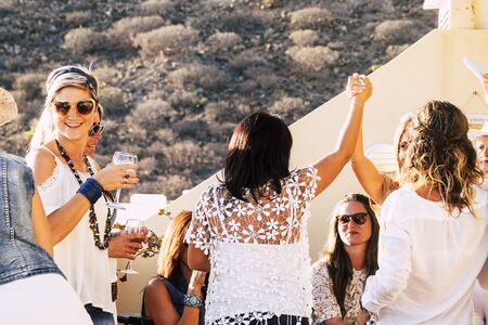 Group of cheerful happy young women celebrate together at home in outdoor terrace with friendship and happiness - concept of friends and smile with dance and drinks