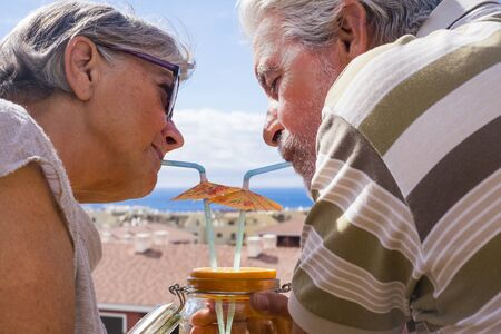 Retired lifestyle with senior people drinking together summer cocktail from same glass - city view and ocean in background - caucasian adults in love