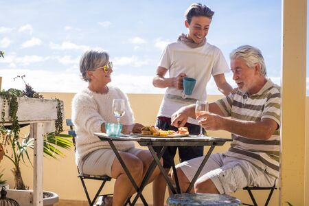 grandfathers adult mature and teenager nephew enjoy outdoor in the terrace some leisure with food and drinks. ocean and city view, vacation sunny day nice weather concept and background. happy people family together
