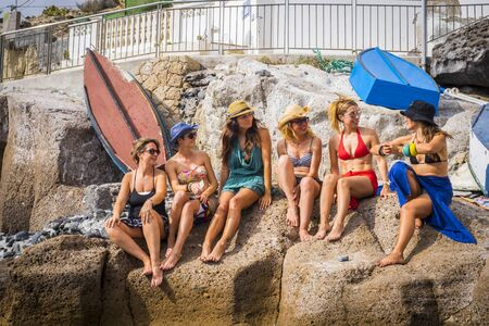 group of nice and beautiful friends smiling together having fun in friendship summer leisure time outdoor near the beach. squimsuits and ladies enjoyed the weather and the sun