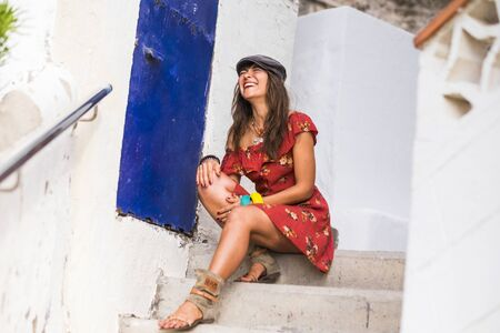 Trendy cheerful caucasian young lady sit down on outdoor white stairs and laugh a lot alone - people having fun and red dress fahsion woman portrait 写真素材