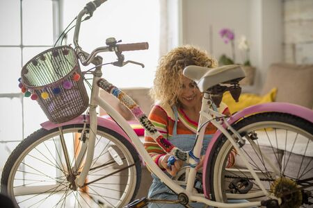 Woman at home doing artwork on a vintage bike - people in quarantine for coronavirus - stay home lockdown concept and indoor activity - diy concept and art female work